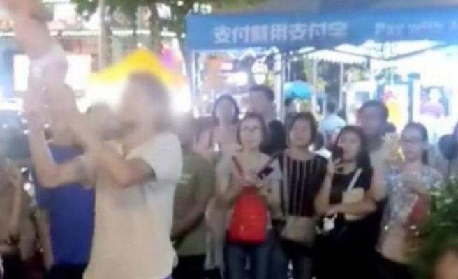 Dört aylık bebeklerini ayaklarından sallayarak ve havada atıp tutarak sokak gösterisi yapan bir Rus çift gözaltına alındı.